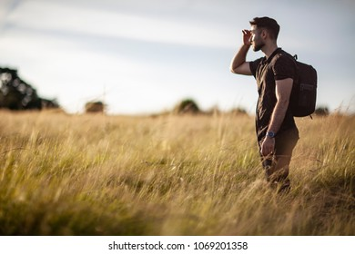 Young male wearing backpack hiking in tall grass looking for directions