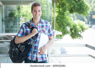 Young male wearing backpack and holding folder