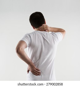 Young male in white t-shirt suffering from neck and back pain. Osteoporosis therapy. Lumbago treatment.
