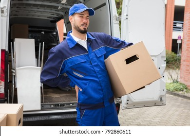 Young Male Worker Carrying Cardboard Box Suffering From Backpain