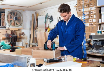 Young male worker  finishing to drill drawer at workshop
