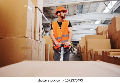 Young male worker in uniform is in the warehouse pushing pallet truck.