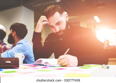 Young male writer get inspired after hard working day and create new poetry or composition in his personal organizing notebook for thoughts while sitting at the table alone in modern coworking office