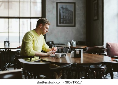 Young male writer wrote his first book on a laptop while sitting in a cozy cafe and drink coffee