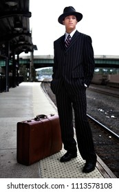 A young man in 1940s style clothes waiting for a train on a train platform