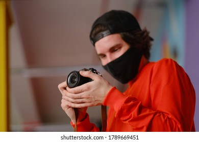 A young man of 25-30 years old in a black protective mask and in a red sweatshirt holds a mirrorless camera in his hands. Male photographer uses a mirrorless camera to take a picture.
