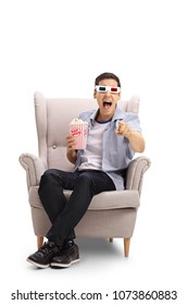 Young man with 3D glasses and popcorn seated in an armchair laughing and pointing at the camera isolated on white background