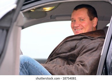 A young man, a man about thirty forty years old sitting in his car and smiling cheerfully.