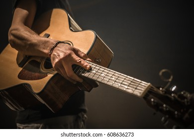 young man with acoustic guitar on black background, creative musical concept