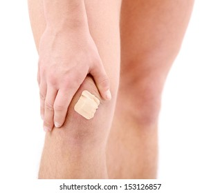 Young man with adhesive bandage on knee, isolated on white