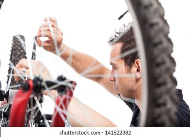 Young man adjusting bike chain and repairing bicycle, isolated on white background