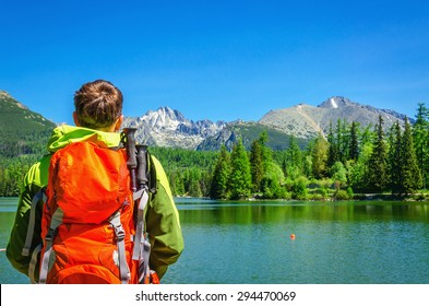 Young man admires beautiful view of the mountain lake Strbske Pleso in National Park High Tatra, Slovakia, Europe