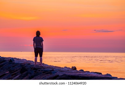 Young man admires the rising sun in June
