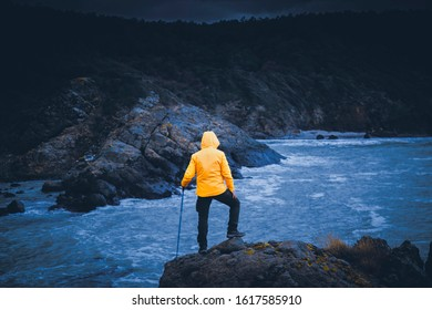 A young man adventurer with contrast yellow jacket posing over cliff by sea under gloomy sky with dramatic clouds