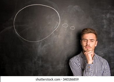 Young  man against the background of chalkboard thinking about the issue