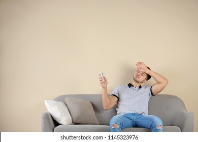 Young man with air conditioner remote suffering from heat at home