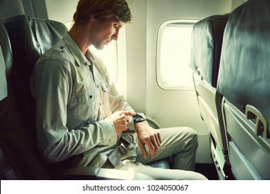 young man in an airplane seat. traveler in an plane looking at watch