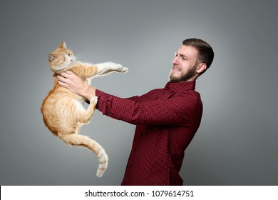 Young man with allergy holding cat on grey background