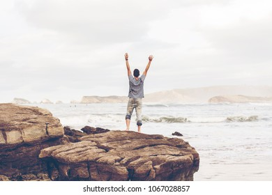 Young man alone in a huge beach