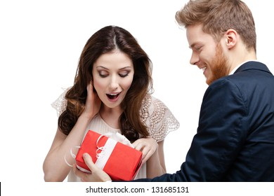 Young man amazes his pretty girlfriend with present wrapped in red paper, isolated on white