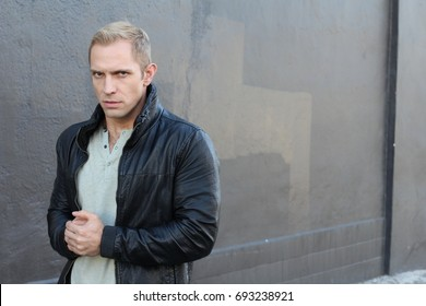 Young man angry gesturing about to raise his fists menacing threat studio portrait on isolated gray background with copy space