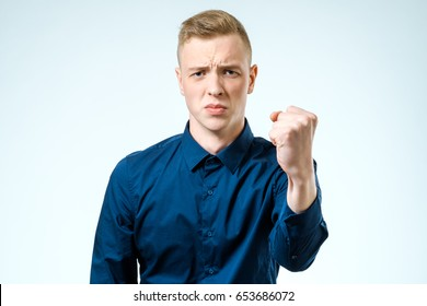 Young man angry gesturing fist raised on isolated white background