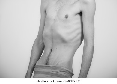 Young man with anorexia nervosa problem. White background.