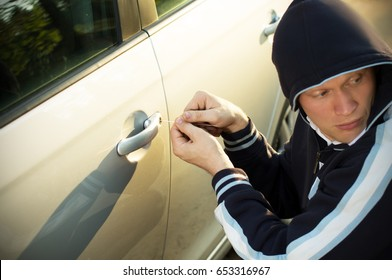 The young man anxiously looking around, steal a car, in the daytime
