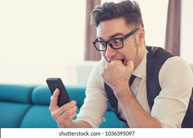 Young man in apartment watching smartphone and biting fist in expression of fear.