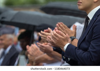 A young man applauds in the crowd in the rain.