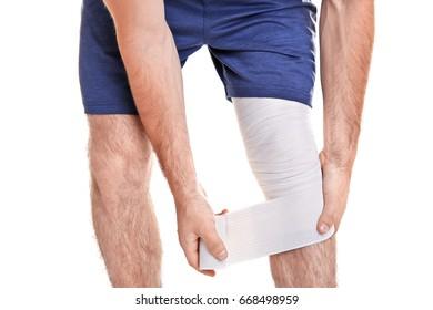 Young man applying bandage onto leg, on white background