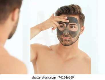 Young man applying cosmetic mask on his face in bathroom