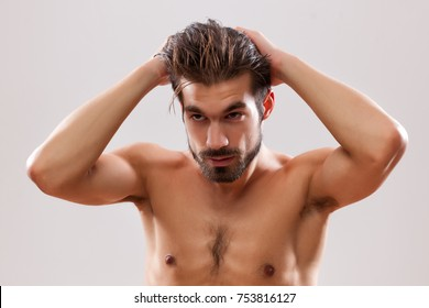 Young man is applying hair gel to his hair.