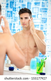young man applying moisturizer on his face front of mirror in bathroom