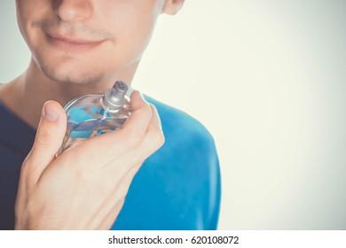 Young man applying perfume on his neck