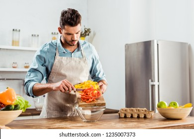 young man in apron preparing vegetable salad in kitchen