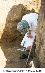 Young man (archaeologist, paleontologist) examines an ancient burial of bones in the burial pit with the help of tools. Archaeological study.Man drawing on graph paper