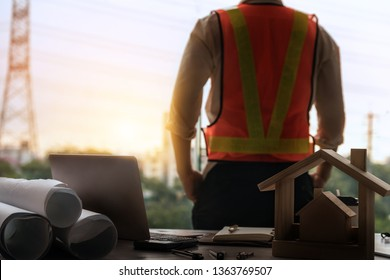 Young man architect or engineer working at desk with designer equipment to make interior design at workplace. Real estate business and civil engineering concept.