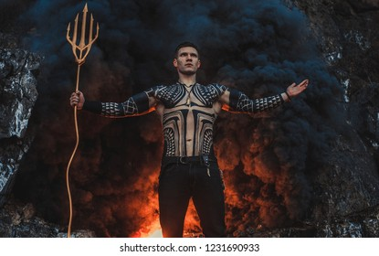A young man in armor and with a trident in his hands against the background of fire and smoke.