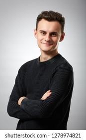 Young man with arms folded, closeup studio shot