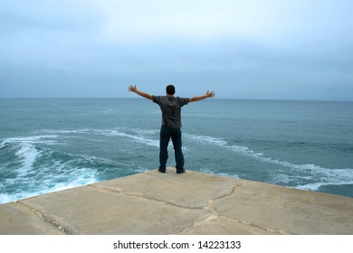 young man with arms open contemplating the ocean