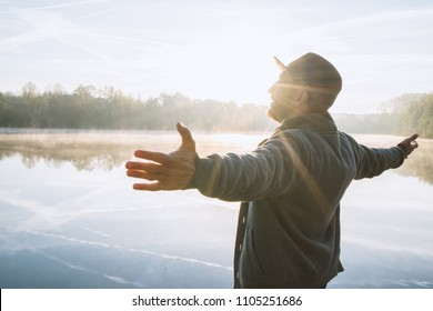 Young man arms outstretched by the lake at sunrise enjoying freedom and life, people travel wellbeing concept. Shot in France, Europe.