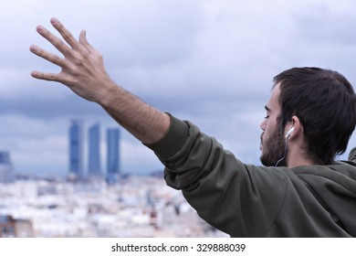 Young man with arms raised madrid towers in the background