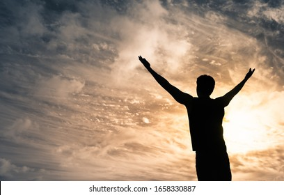 Young man with arms up to the sky feeling happy with positive feelings.