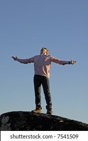 young man with arms wide open and the sky as background