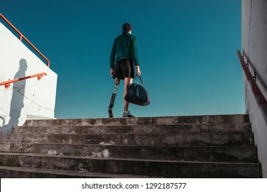 Young man with artificial leg staying at the stairs at stadium and preparing for workout
