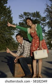 Young man and asian girl with a big smile have their thumbs out to hitch a ride along the roadside. They are traveling with their suit cases.