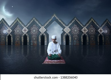 Young man Asian moslem pray on the night with mosque and moon background