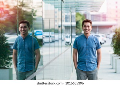 Young man asian smiling and looking at camera. Portrait of a happy handsome young man beside modern building. Close up face of young cool trendy man looking at camera