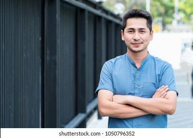 Young man Asian smiling and looking at camera. Portrait of a happy handsome young man in a urban street. Close up face of young cool trendy man looking at camera